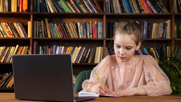 Девушка в розовой блузке смотрит на экран ноутбука и пишет в тетрадке, сидя за деревянным столом на фоне цветных книг на полках в библиотеке