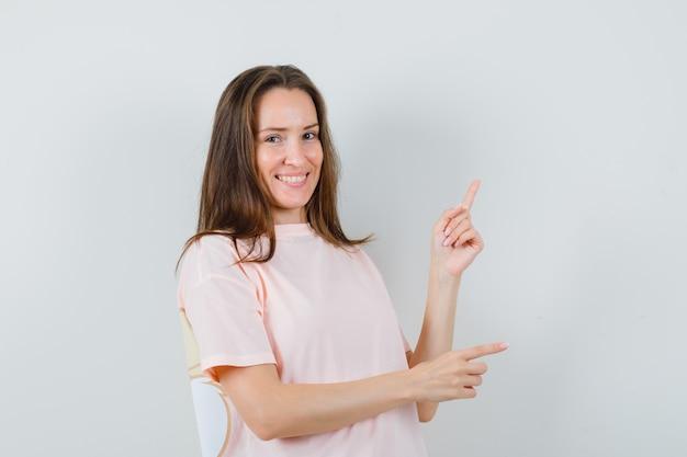 ピンクのtシャツを着た若い女性が上を向いて脇を向いて陽気に見えます