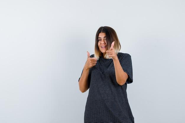 Молодая дама в платье-поло, указывая на камеру и глядя счастливым, вид спереди.
