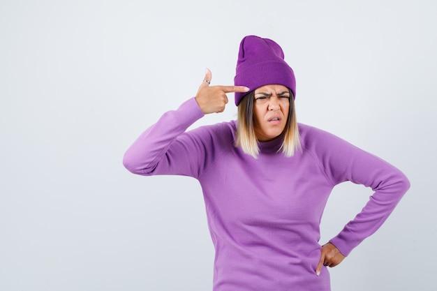 紫色のセーターを着た若い女性、こめかみに指を持って真剣に見えるビーニー、正面図。