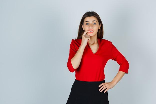 赤いブラウスを着た若い女性、腰に手を当てて怖がっているように見えながら指を噛むスカート