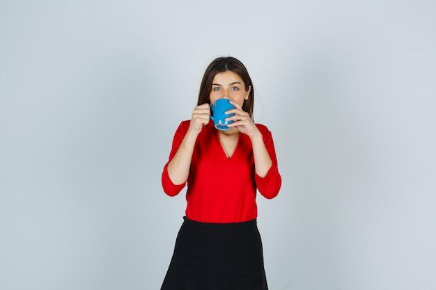赤いブラウスを着た若い女性、立って喜んで見ながらスカートを飲む