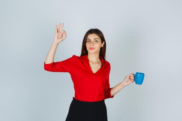 빨간 블라우스에 젊은 아가씨, 확인 제스처를 보여주는 동안 컵을 들고 치마