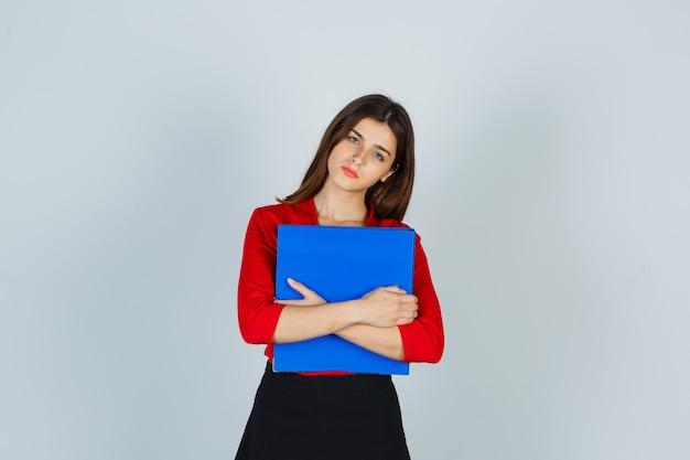 赤いブラウスの若い女性、胸にフォルダーを保持し、物思いにふけるスカート