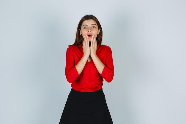 赤いブラウス、あごに手をつないで困惑しているスカートの若い女性