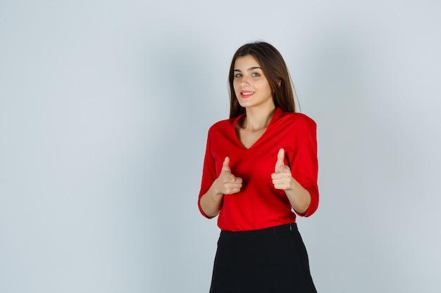 Девушка в красной блузке, юбка, указывающая на камеру и великолепно выглядящая