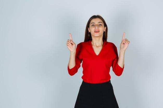 赤いブラウスを着た若い女性、上を向いて陽気に見えるスカート