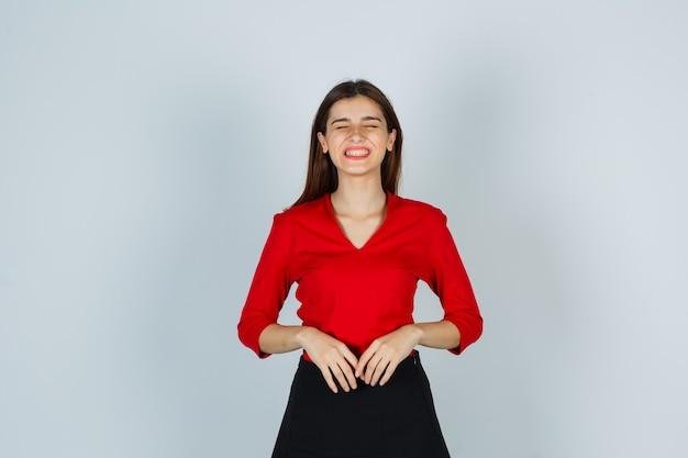 Молодая дама в красной блузке, юбке показывает зубы и выглядит смешно