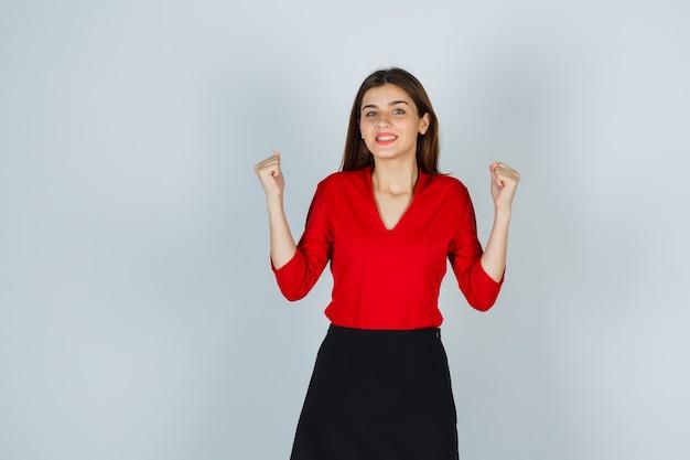 빨간 블라우스에 젊은 아가씨, 승자 제스처를 보여주는 치마와 행복한 찾고