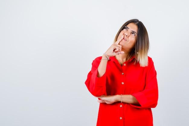 赤い特大のシャツを着た若い女性が口に指を持ち、思慮深く、正面から見ています。