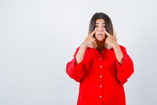 赤い特大のシャツを着た若い女性は、頬に指を持ち、焦点を合わせて、正面図を探しています。