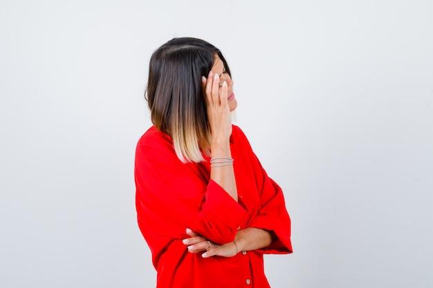 Девушка в красной рубашке oversize, склонив голову на руку и усталая, вид спереди.
