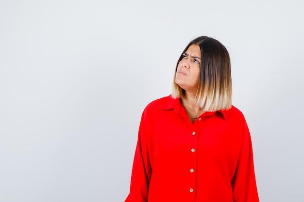 脇を見て真剣に見える赤い特大のシャツを着た若い女性、正面図。