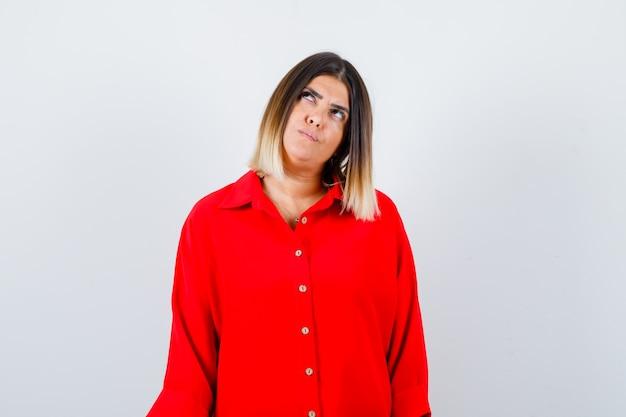 Молодая дама в красной рубашке oversize смотрит в сторону и смотрит задумчиво, вид спереди.
