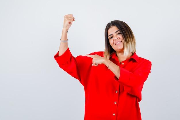 빨간색 특대형 셔츠를 입은 젊은 여성이 팔 근육을 가리키고 기뻐하며 정면을 바라보고 있습니다.