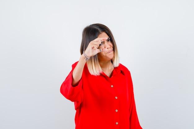 Молодая дама в красной рубашке негабаритного размера, показывающая знак небольшого размера и серьезная, вид спереди.
