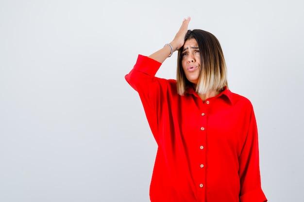 머리에 손을 대고 건망증을 찾고 있는 빨간색 특대형 셔츠를 입은 젊은 여성, 전면 보기.
