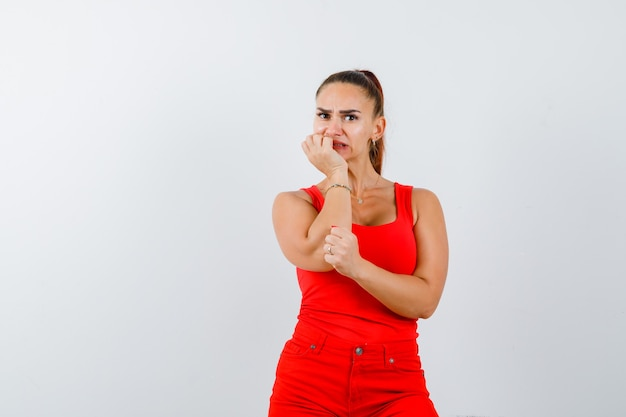赤い一重項の若い女性、手にあごを支え、心配そうに見える赤いズボン、正面図。