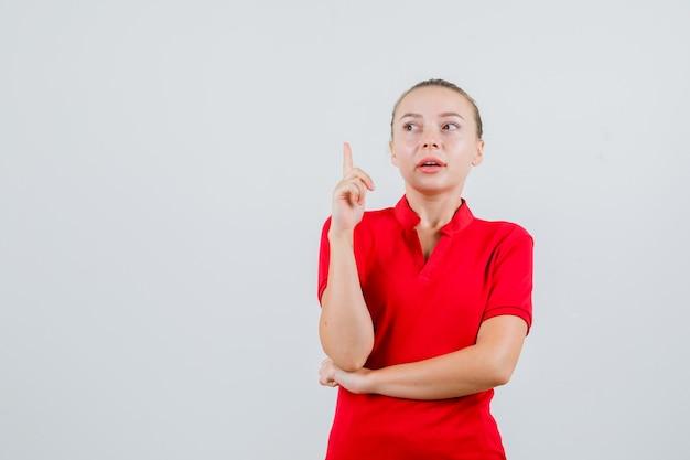 빨간 t- 셔츠를 가리키고 집중 찾고 젊은 아가씨