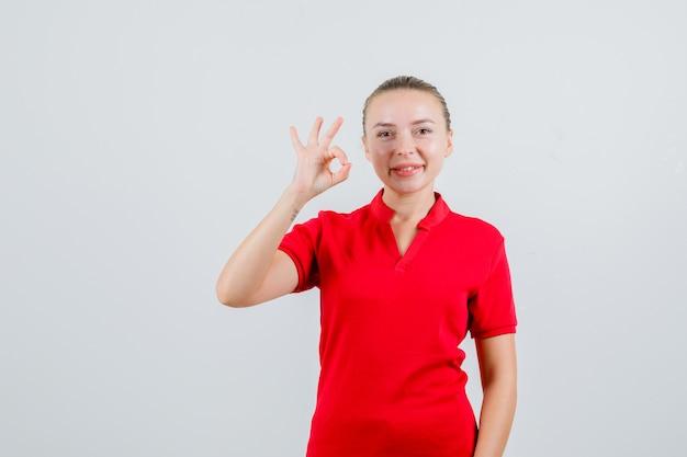 良いジェスチャーを示し、満足そうに見える赤いtシャツの若い女性