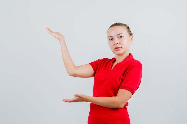 환영 또는 뭔가 보여주는 빨간 티셔츠에 젊은 아가씨