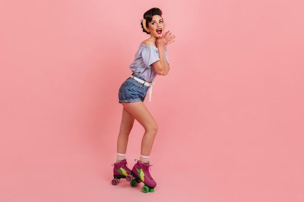 ピンクの背景で叫んでローラースケートの若い女性。ファッショナブルなピンナップガールのスタジオショット。