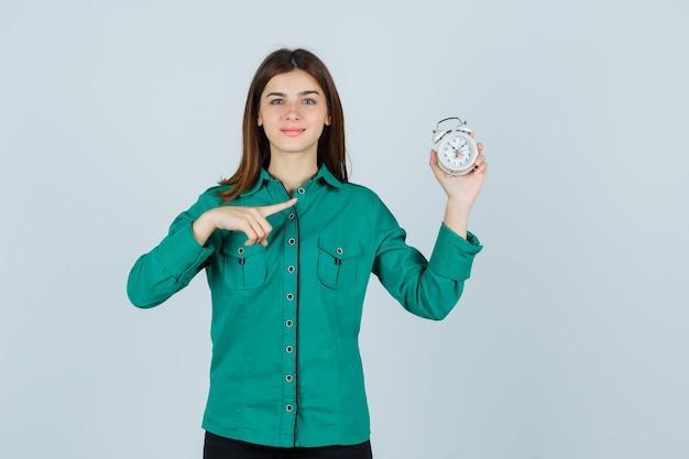 目覚まし時計を保持し、それを指して、喜んでいるシャツを着た若い女性、正面図。