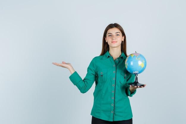 Молодая дама в рубашке держит земной шар, делает приветственный жест и выглядит довольным, вид спереди.