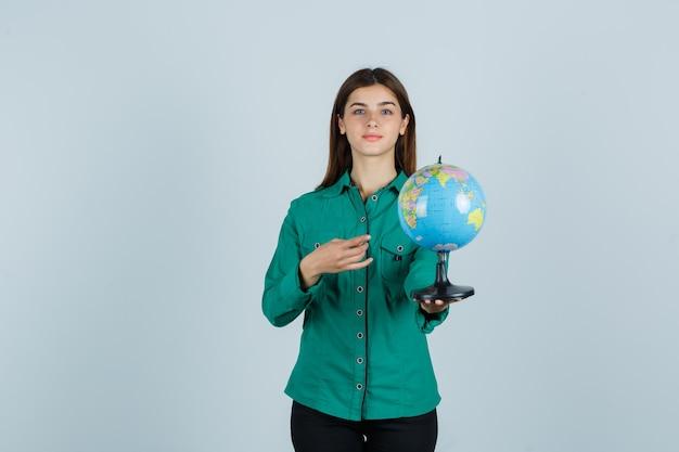 지구 글로브를 들고, 그것을 가리키고 자신감, 전면보기를 찾고 셔츠에 젊은 아가씨.