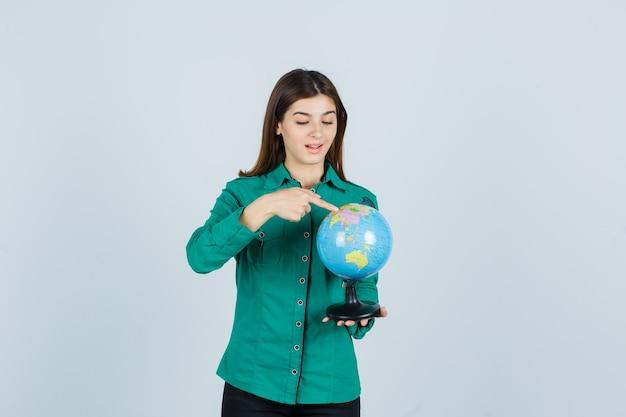 지구 지구본을 들고, 그것을 가리키고 흥분, 전면보기를 찾고 셔츠에 젊은 아가씨.