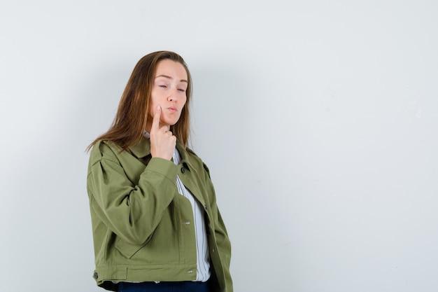 頬に指を保持し、物思いにふける、正面図を見てシャツの若い女性。