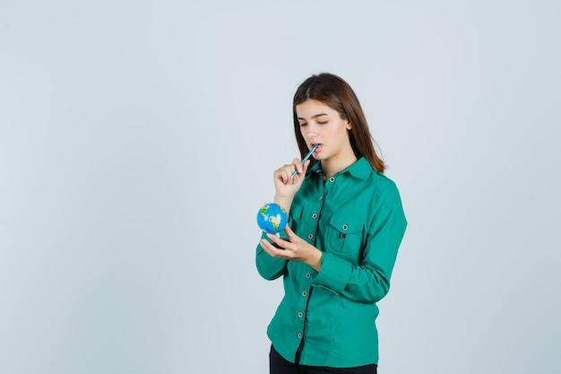 ペンを口の中に保ち、物思いにふける、正面図を見て地球儀を保持しているシャツの若い女性。