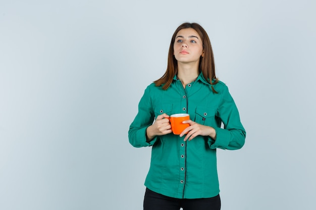 오렌지 차 한잔 들고 자신감, 전면보기를 찾고 셔츠에 젊은 아가씨.
