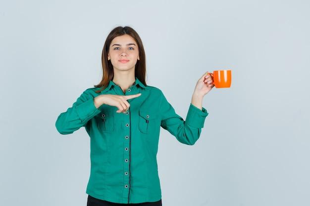 右側を指して、自信を持って、正面図を見て、オレンジ色のお茶を持っているシャツを着た若い女性。
