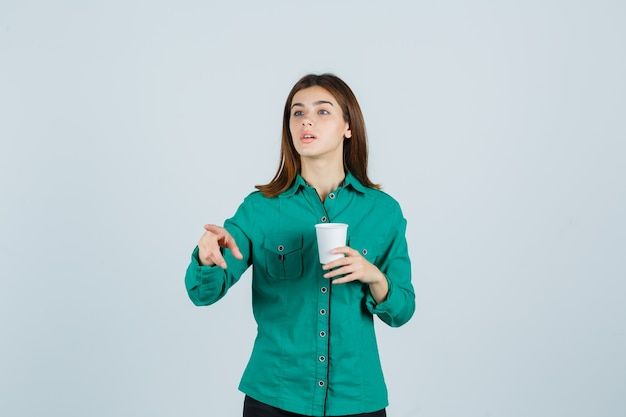 Молодая дама в рубашке держит пластиковую чашку кофе, указывая в сторону и смотрит сосредоточенно, вид спереди.