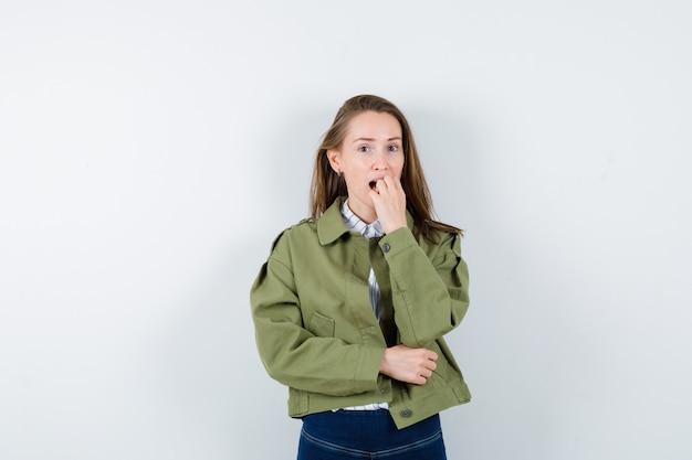 シャツを着た若い女性、彼女の爪を噛み、驚いたように見えるジャケット、正面図。