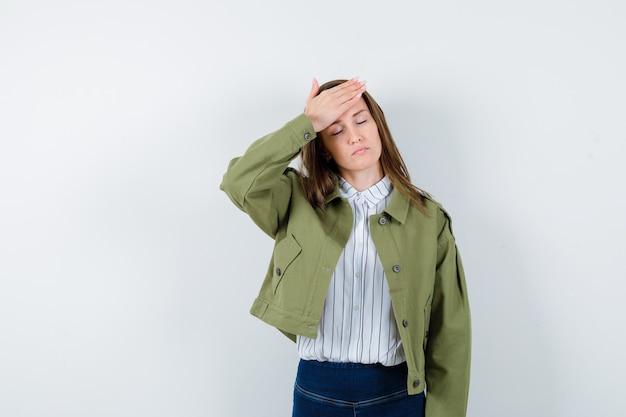 シャツを着た若い女性、額に手を握り、疲れているように見えるジャケット、正面図。