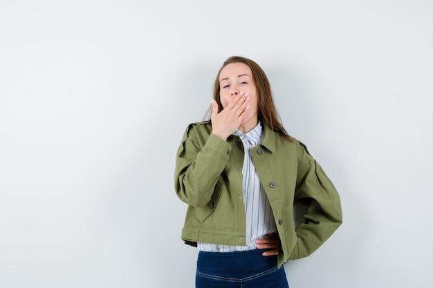 シャツを着た若い女性、あくびをしながら眠そうな顔をしている間、口に手をかざすジャケット、正面図。