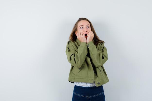 シャツを着た若い女性、開いた口の近くで手を握り、怖がって見えるジャケット、正面図。