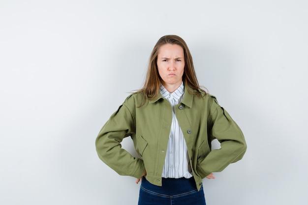 シャツを着た若い女性、腰に手をつないで、疑わしい、正面図を見てジャケット。