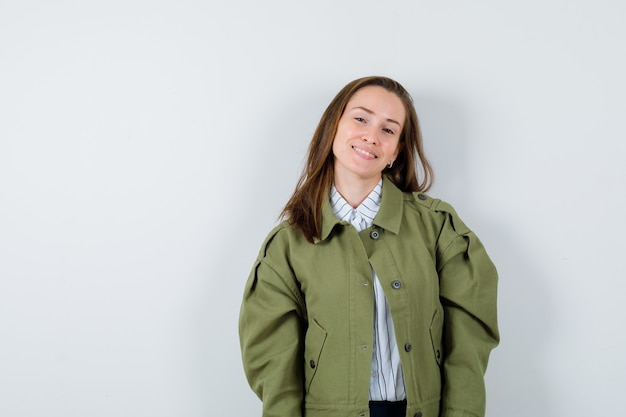 Молодая дама в рубашке, куртке смотрит в камеру и выглядит привлекательно, вид спереди.