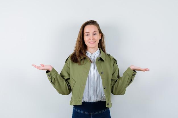 シャツを着た若い女性、体重計のジェスチャーをし、陽気に見えるジャケット、正面図。