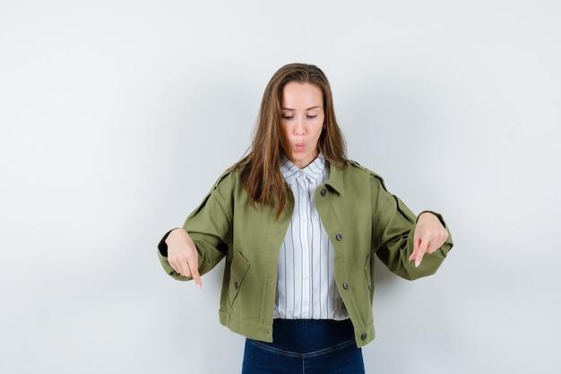 シャツを着た若い女性、下を向いて焦点を合わせたジャケット、正面図。