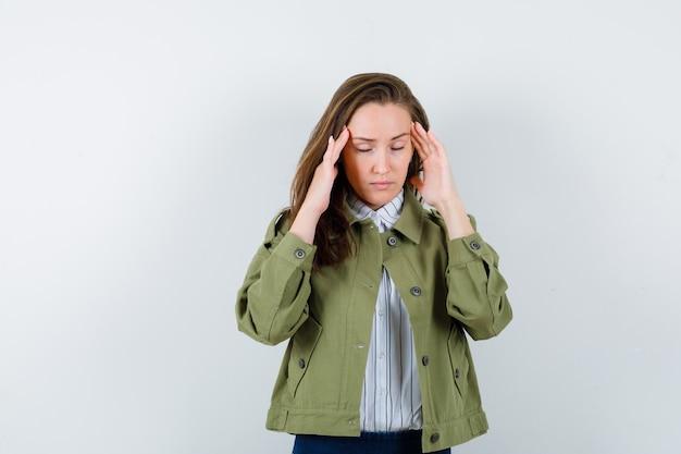シャツを着た若い女性、ジャケットがこめかみをこすり、頭痛がして、疲れているように見える、正面図。