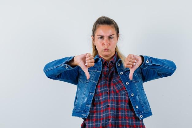 シャツを着た若い女性、二重の親指を下に向けて暗い顔をしているジャケット、正面図。