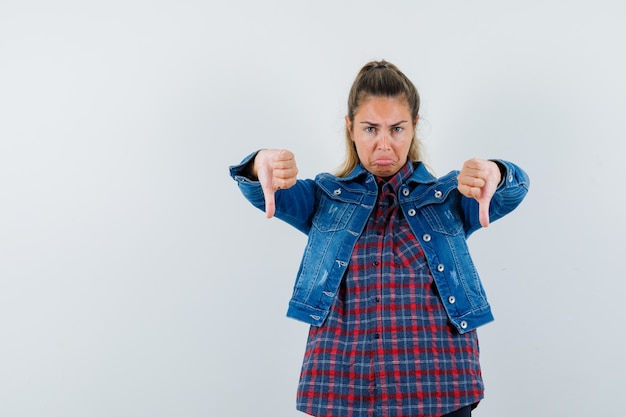 シャツを着た若い女性、二重の親指を下に向けて悲しそうに見えるジャケット、正面図。