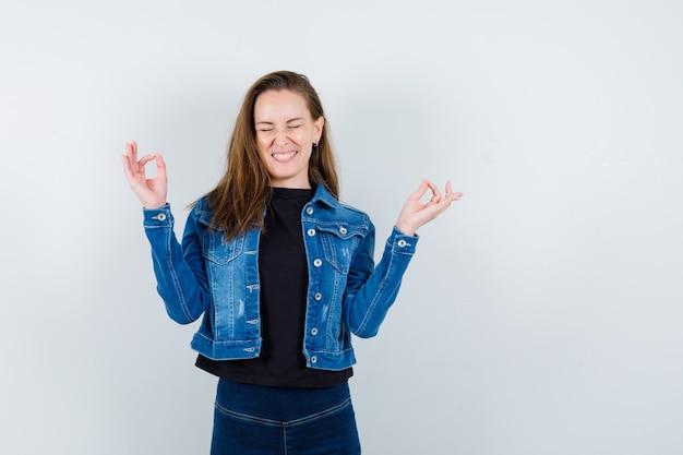 シャツを着た若い女性、瞑想のジェスチャーを示し、至福に見えるジャケット、正面図。