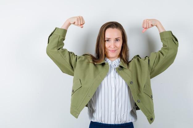 Молодая дама в рубашке, куртке показывает мышцы рук и выглядит уверенно, вид спереди.