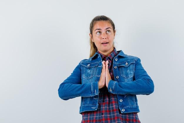 シャツを着た若い女性、ナマステのジェスチャーを示し、希望に満ちた正面図を示すジャケット。