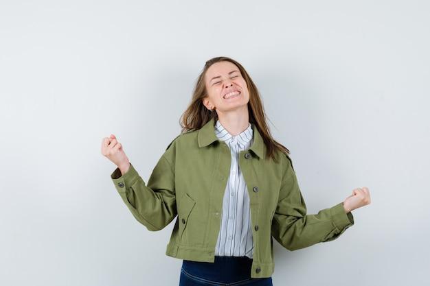 シャツを着た若い女性、勝者のジェスチャーを示し、至福の正面図を示すジャケット。